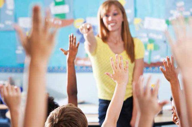 students raise their hands in classroom