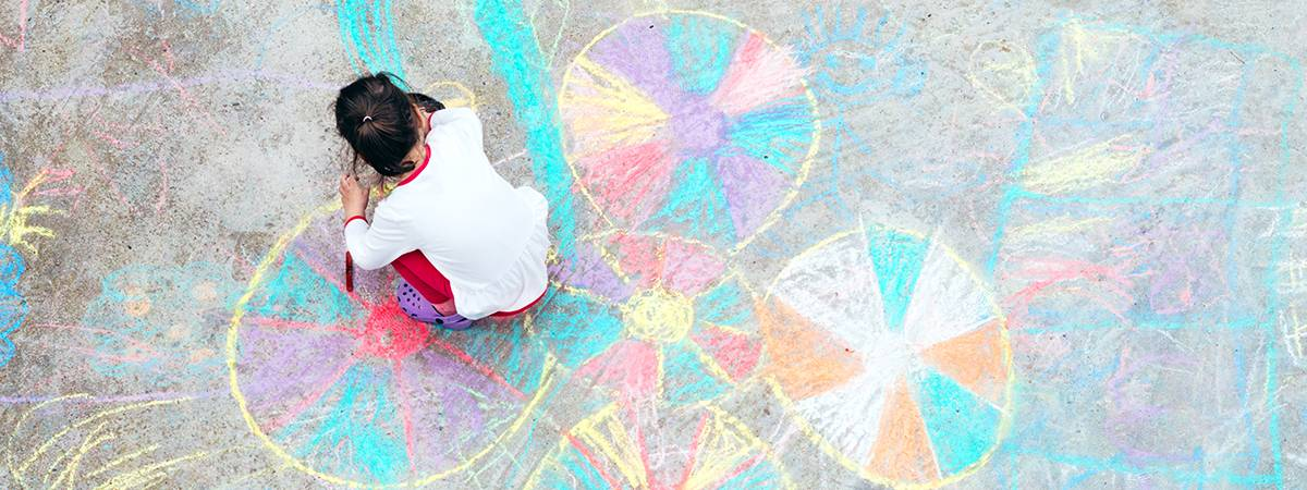 Little girl drawing with chalk on the sidewalk