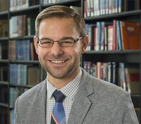 A male-presenting person smiles towards the camera in a library.