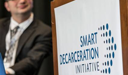 """A podium with a logo on the front that reads: """"Smart Decarceration Initiative"""""""