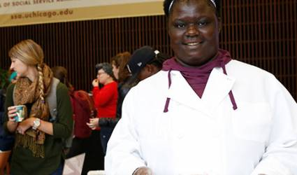 A female-presenting person in a chef's gown looks towards the camera.
