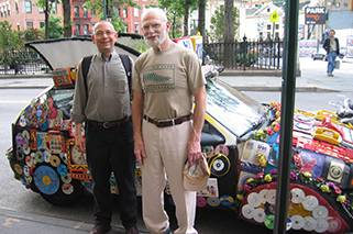 Bill and Oliver stand in front of a heavily decorated art car