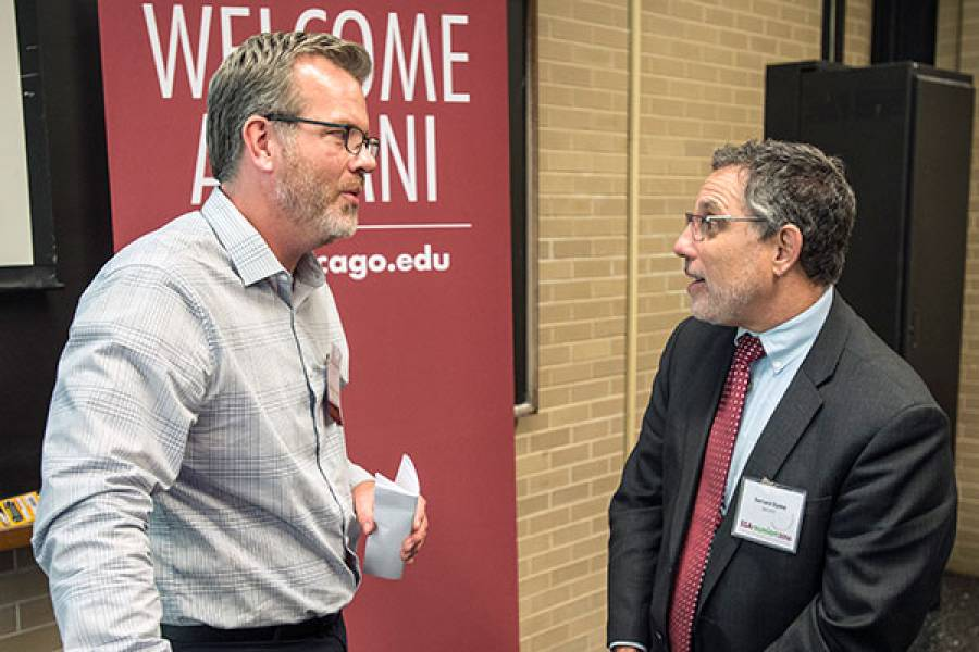 Associate Professor Matt Epperson discusses with an alumni after his presentation