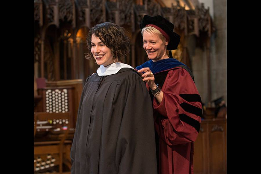 Lecturer Jessica Darrow assists in the Hooding Ceremony